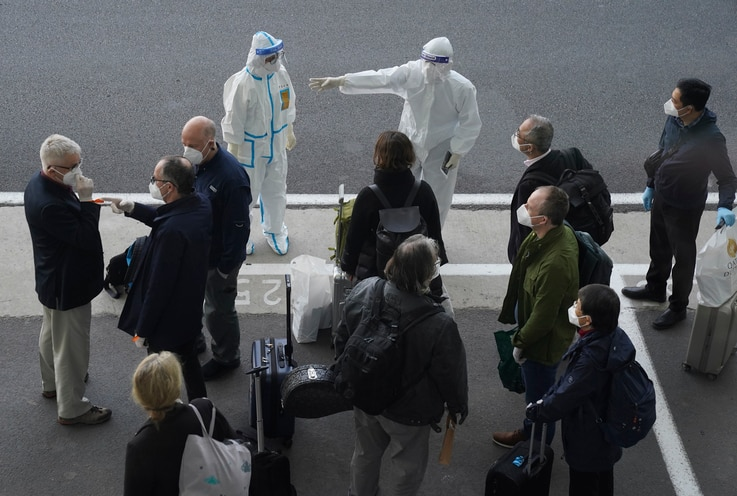 A worker in protective coverings directs members of the World Health Organization (WHO) team on their arrival at the airport in…