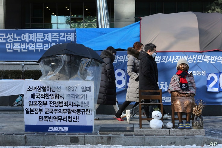 A protester sits next to a statue symbolizing a wartime sex slave to demand full compensation and an apology for wartime sex…