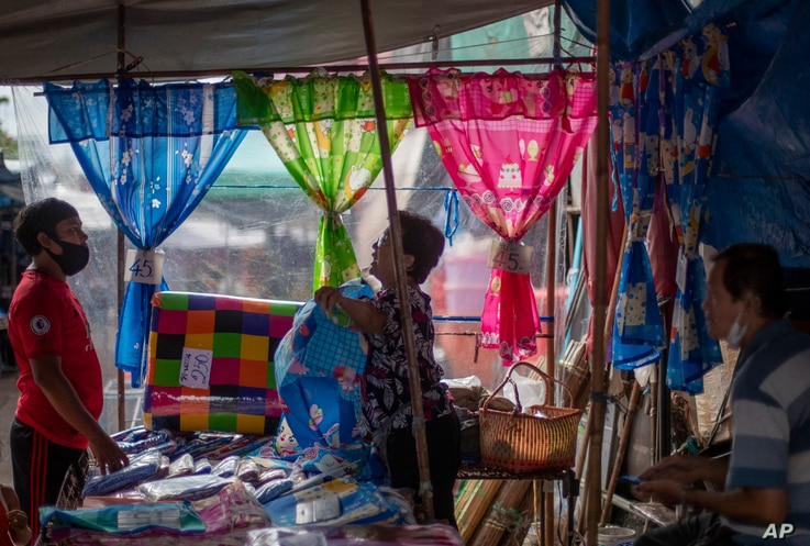 A fabric vender negotiates with a buyer at a roadside shop in Bangkok, Thailand, Wednesday, Aug. 5, 2020. Thailand has managed…