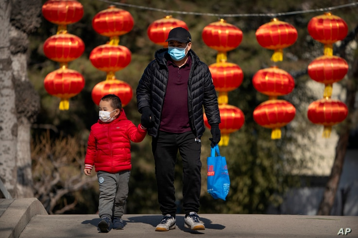 A man and child wearing face masks to protect against the spread of the coronavirus walk past lanterns at a public park in…