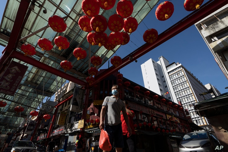 A Chinese couple wear face mask walks with Chinese lunar new year decoration at China town in Kuala Lumpur, Malaysia, Sunday,…