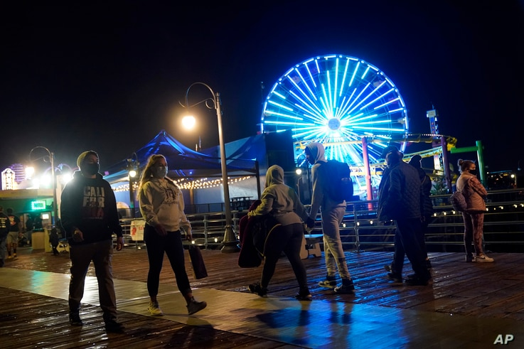 Visitors wear face masks while walking the pier amid the COVID-19 pandemic Friday, Feb. 19, 2021, in Santa Monica, Calif. (AP…