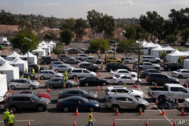 Motorists line up for their COVID-19 vaccine a joint state and federal mass vaccination site set up on the campus of California…
