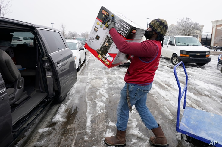 Lowes' employee Jalend Washington carries a kerosene heater to a customer's van, Thursday, Feb. 18, 2021, in Madison, Miss. Sub…