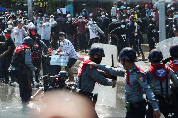 Protesters run after police fire warning-shots and use water cannons to disperse them during a protest in Mandalay, Myanmar on…