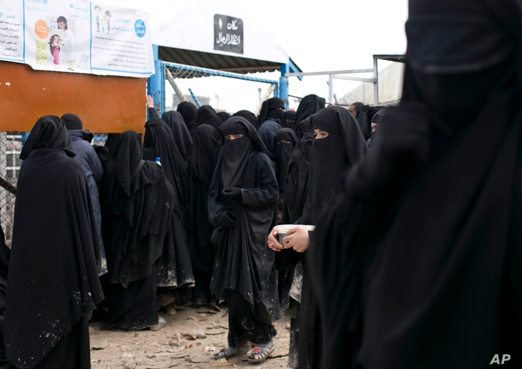 FILE -  In this Sunday, March 31, 2019, file, photo, women line up for aid supplies at Al-Hol camp in Hassakeh province, Syria…