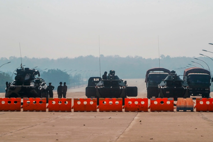 Myanmar's military stand guard at a checkpoint manned with an armored vehicles blocking a road leading to the parliament…