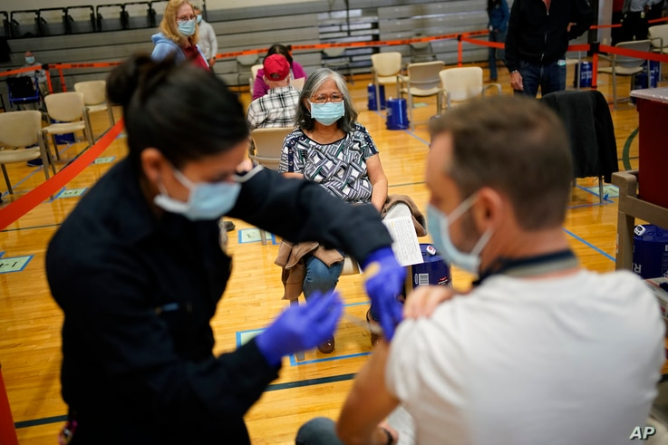 People receive the COVID-19 vaccine at a vaccination site Wednesday, Feb. 17, 2021, in Las Vegas. (AP Photo/John Locher)
