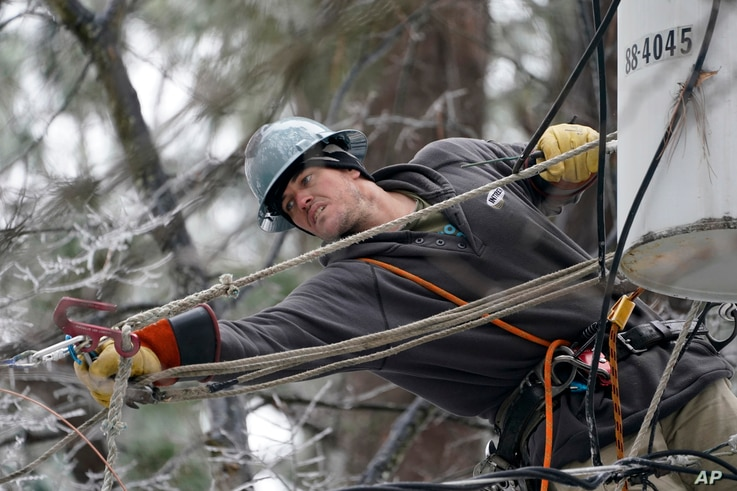 Lineman Charlie Hofmann stretches for a cable as he repairs a transformer in Jackson, Miss., Thursday, Feb. 18, 2021. Hofmann,…