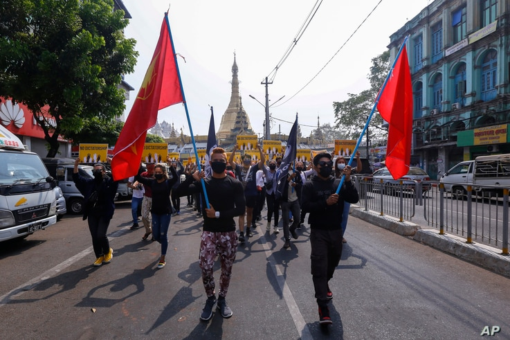 Anti-coup protesters march with flag during a demonstration in Yangon, Myanmar, Friday, March 26, 2021. Protesters against last…