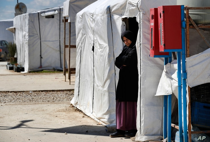 A Syrian displaced woman stands at the entrance of her tent at a refugee camp, in Bar Elias, in eastern Lebanon's Bekaa valley,…