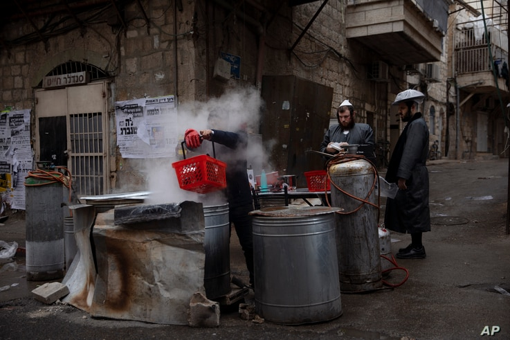 An ultra-Orthodox Jewish man dips cooking utensils in boiling water to remove remains of leaven in preparation for the upcoming…