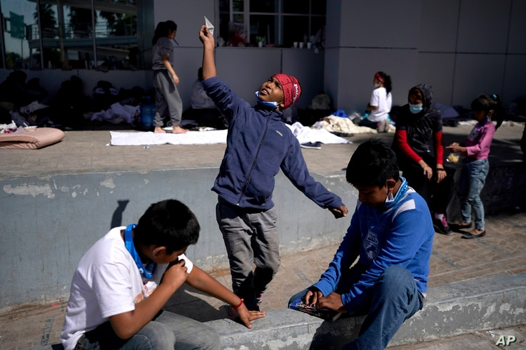 A migrant boy, center, launches a paper airplane while playing with other migrant kids at a plaza near the McAllen-Hidalgo…