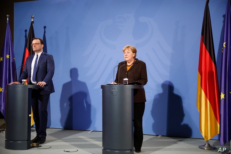 German Chancellor Angela Merkel, right, and Health Minister Jens Spahn brief the media after a virtual meeting with federal…