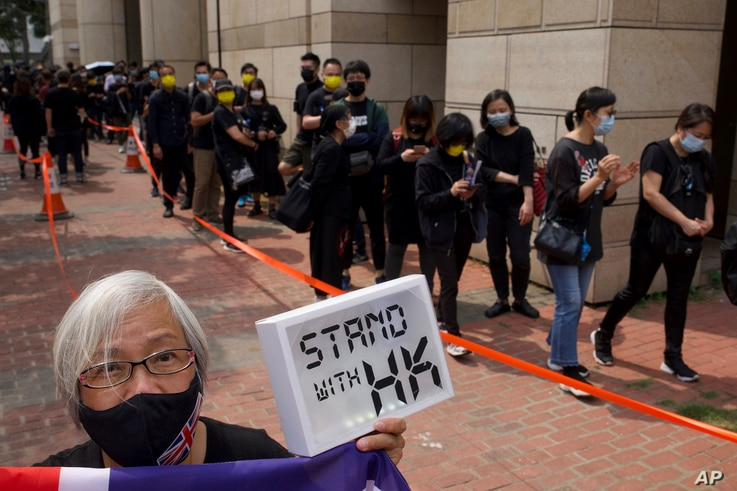 A woman holds a placard as supporters queue up outside a court to try to get in for a hearing in Hong Kong Monday, March 1,...