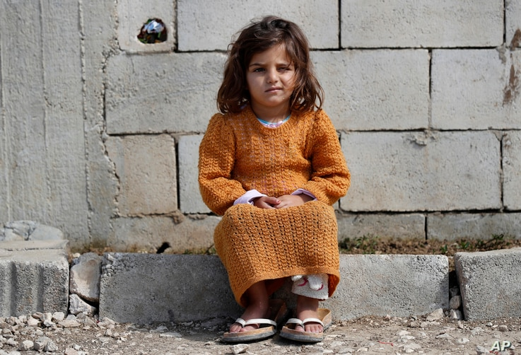 A displaced Syrian girl sits outside her family's tent at a refugee camp in Bar Elias, Bekaa Valley, Lebanon, Friday, March 5,…