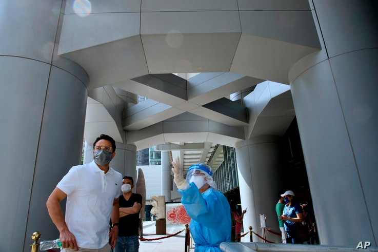A staff member in a protective suit directs a HSBC staff to a temporary testing center for COVID-19 near the entrance to the…
