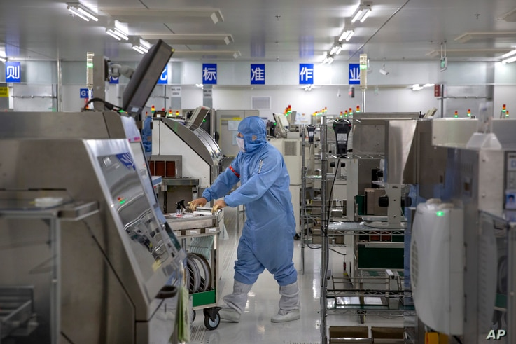 An employee wearing protective equipment pushes a cart at a semiconductor production facility for Renesas Electronics during a…