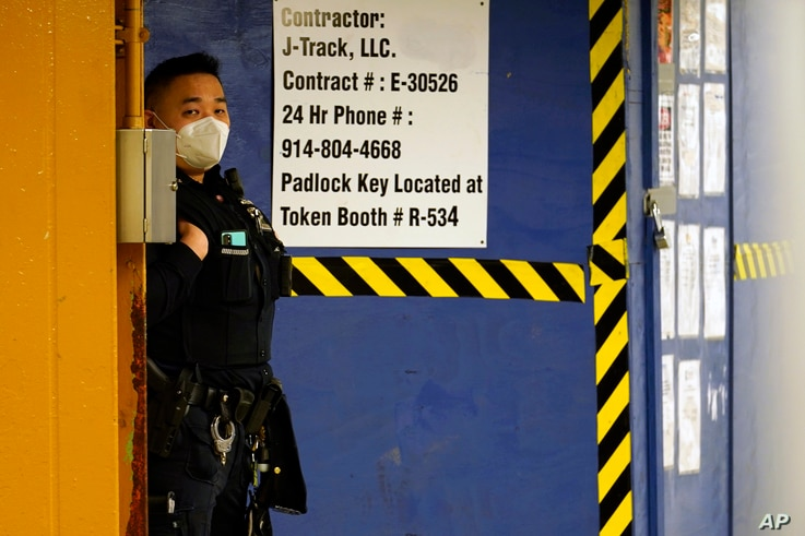 "An Asian American New York City Police officer patrols inside the ""7"" train station beneath a heavily trafficked section of…"