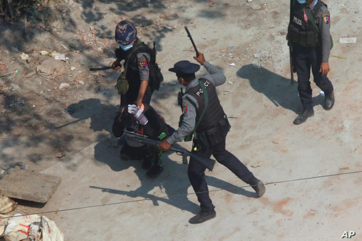 Riot police officers hold down a protester as they disperse protesters in Tharkata Township on the outskirts of Yangon, Myanmar…