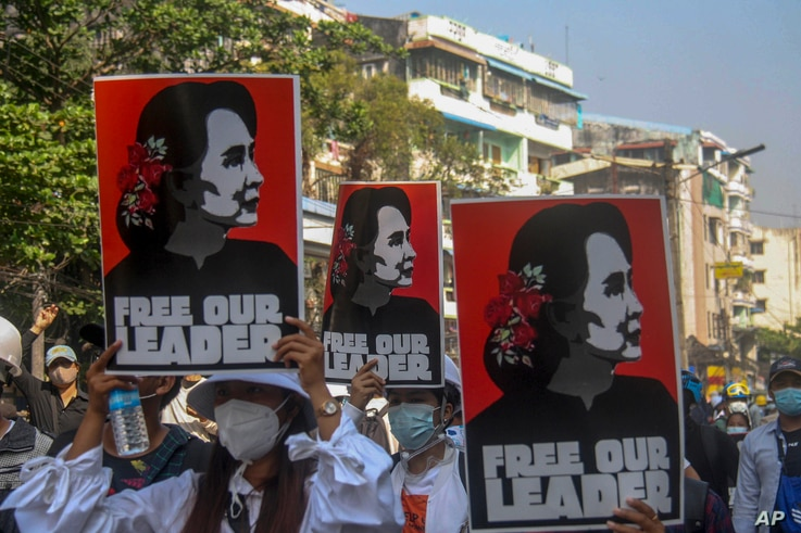 Anti-coup protesters display pictures of deposed Myanmar leader Aung San Suu Kyi in Yangon, Myanmar, Tuesday, March 2, 2021...
