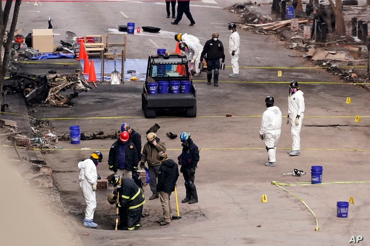 FBI and ATF personnel examine the area involved in a Christmas Day explosion Tuesday, Dec. 29, 2020, in Nashville, Tenn…