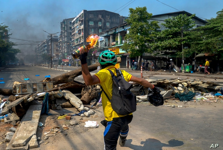 An anti-coup protester throws a molotov cocktail towards police as they move towards the protest area in Yangon, Myanmar…