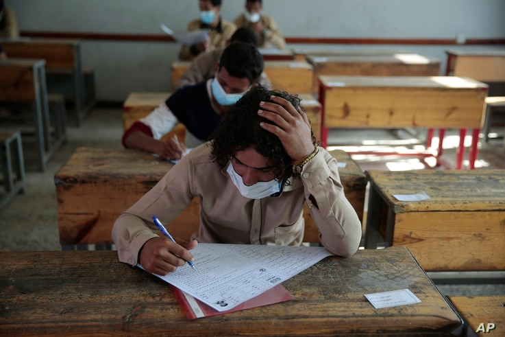 Yemen students wear face masks to help curb the spread of the coronavirus (COVID-19) as they take a final-term school exam at a…