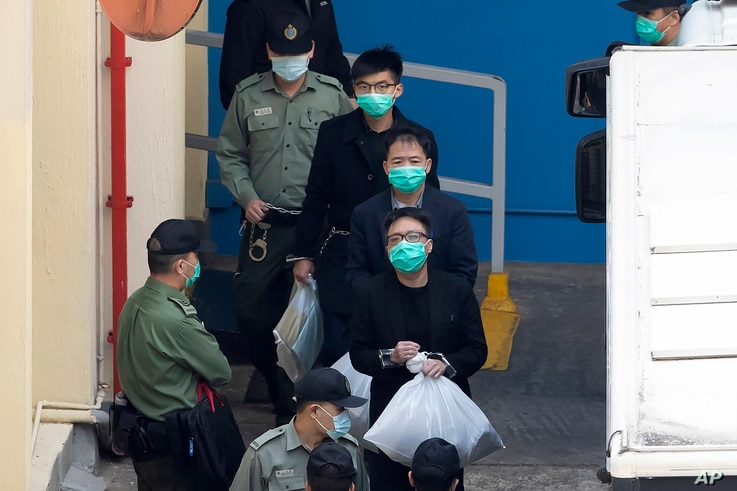 From top, Joshua Wong, Wu Chi-wai and Tam Tak-chi, some of the 47 pro-democracy Hong Kong activists, are escorted by…