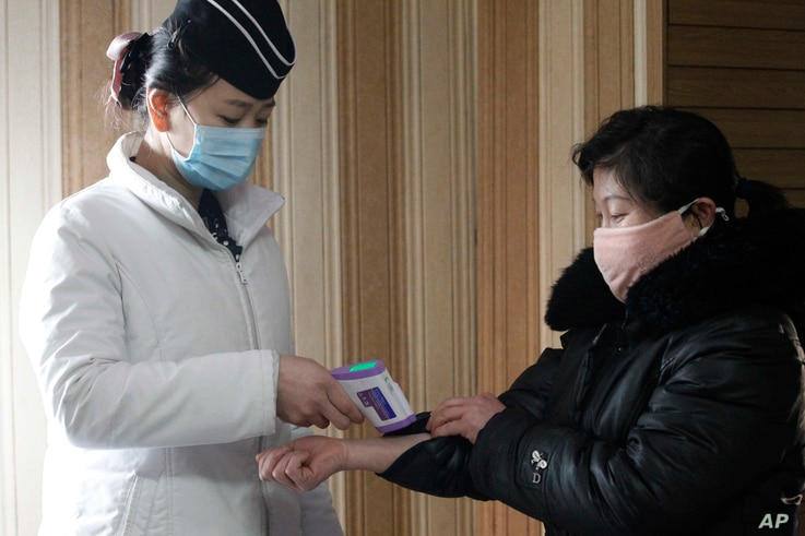 A staff member, left, of the Pongnam Noodle House checks the body temperature of a woman coming into its restaurant in…