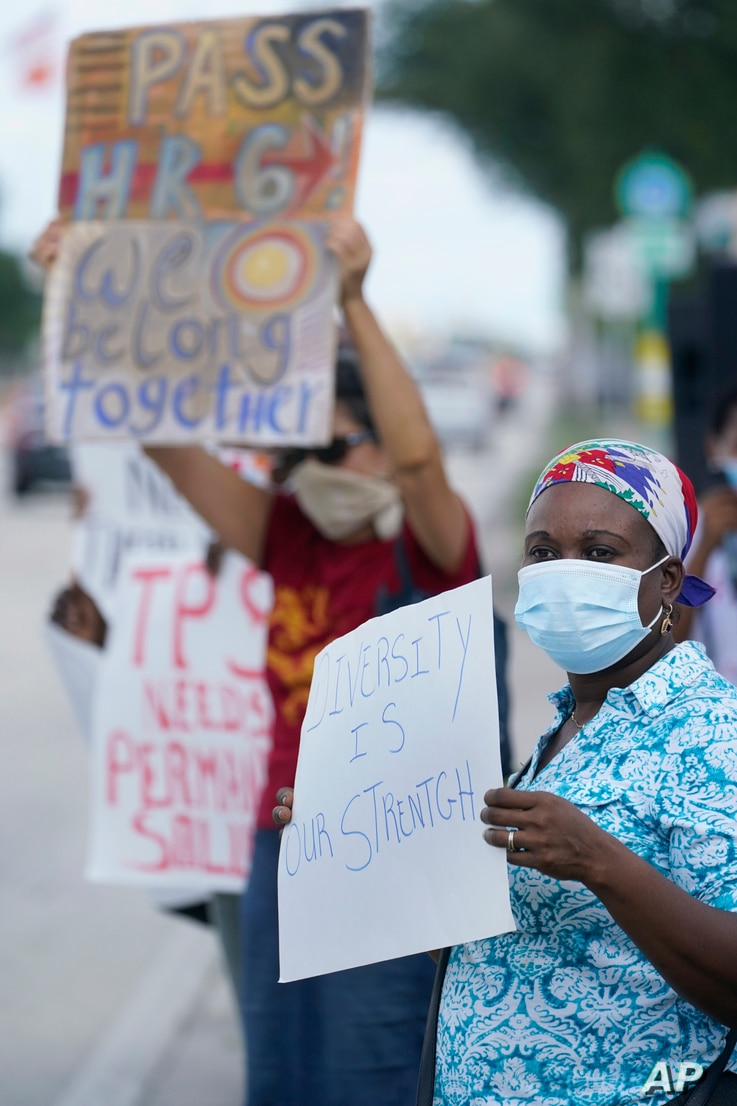 Temporary Protected Status (TPS) holder Kerlyne Paraison, foreground, of Haiti, holds up a sign as she demonstrates during a…