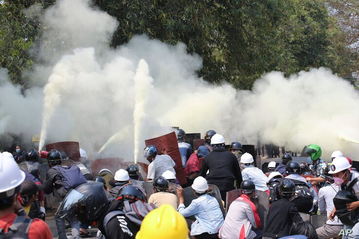 Anti-coup protesters discharge fire extinguishers to counter the impact of the tear gas fired by police during a demonstration…