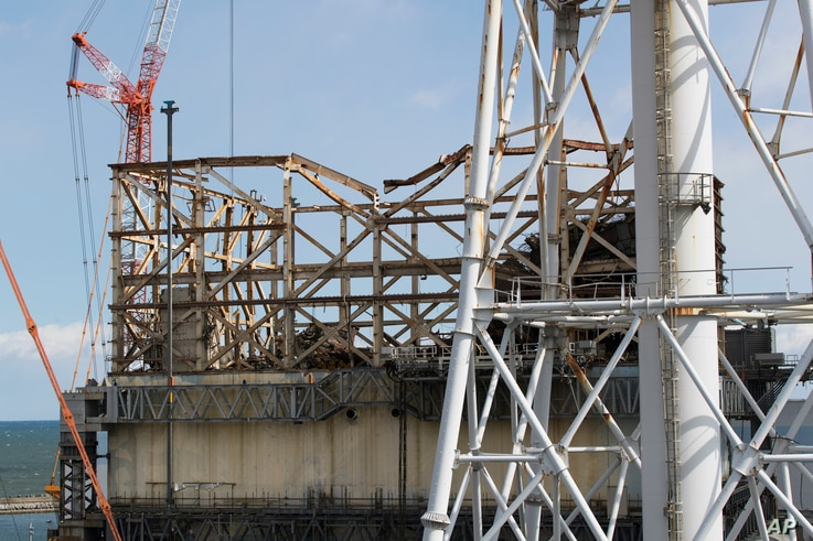 This photo shows the damaged Unit 1 reactor, back, and the exhaust stack shared with the Unit 1 and 2 reactors at the Fukushima…