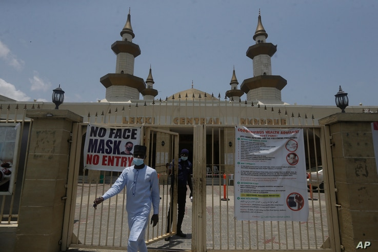 A Muslim man walk past Covid-19 guidelines at the gate of Lekki Central mosque, in Lagos Nigeria, Friday, April 16, 2021…