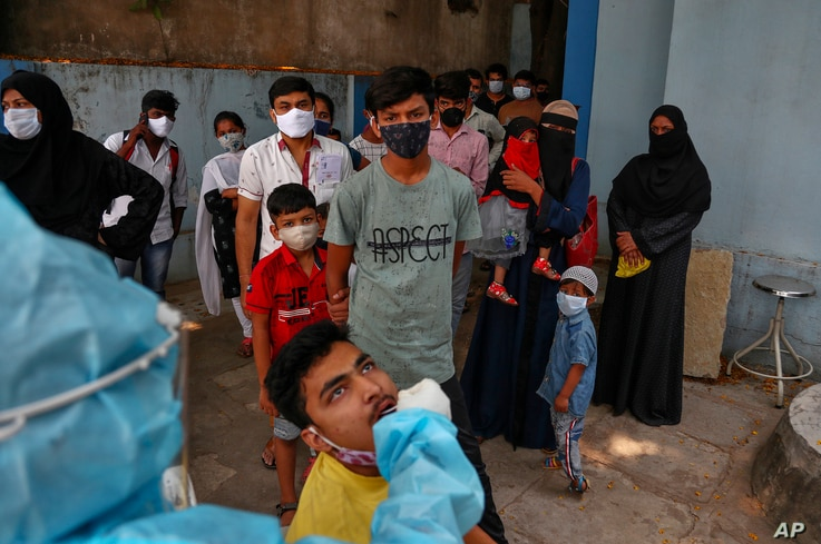 A health worker takes a nasal swab sample of a man to test for COVID-19 as others wait their turn to get tested at a hospital…