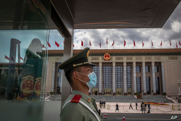 A Chinese People's Liberation Army (PLA) soldier wearing a protective face mask stands guard in front of the Great Hall of the…