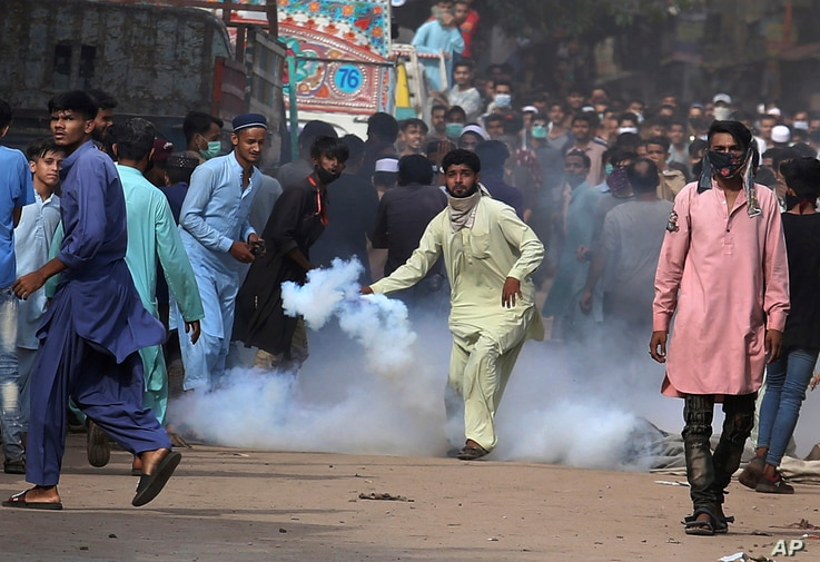 A supporters of Tehreek-e-Labiak Pakistan, a banned Islamist party, prepares to hurl back a tear gas canister fired by police...