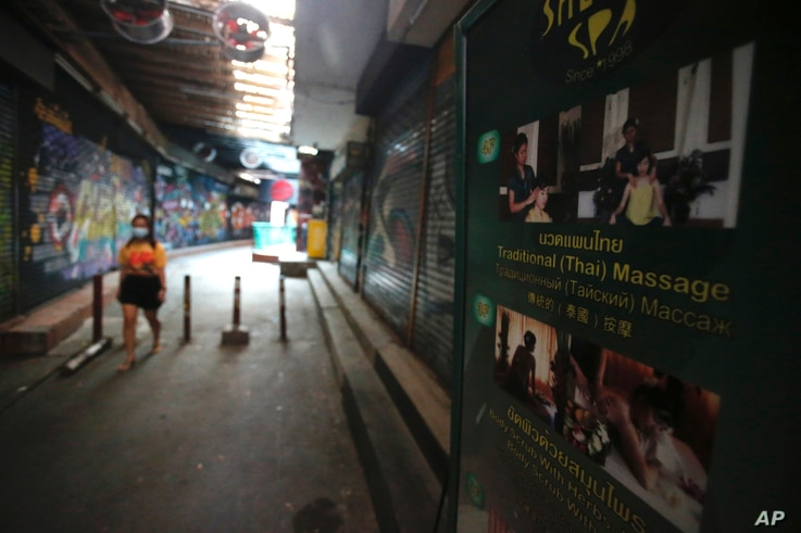 A passerby wearing a face mask to help curb the spread of the coronavirus moves past a closed massage shop in Khao San road, a...