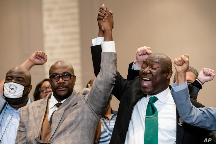 Philonise Floyd, brother of George Floyd, left, and attorney Ben Crump, right, raise their hands in triumph during a news…