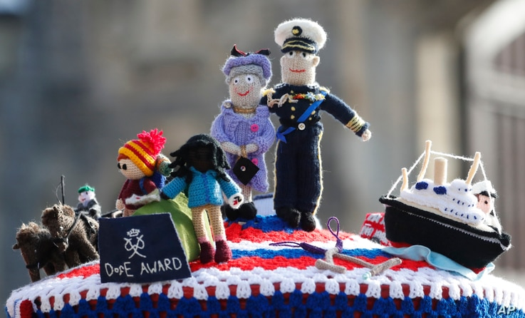 A knitted top cover for a post box depicting Britain's Queen Elizabeth II and her husband Prince Philip in Windsor, England,…
