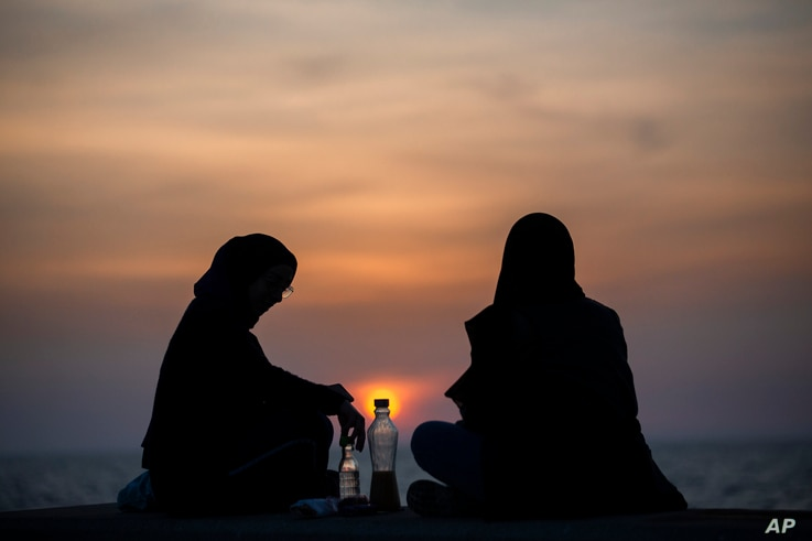 Muslim women attend the sun sets to break their fast, during the Muslim holy fasting month of Ramadan along the seaside…