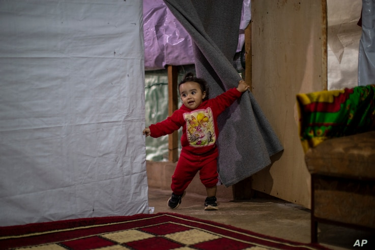 Syrian refugee Rayan, 18 months old, plays inside her parents' tent before they break their fast on the first day of fasting...