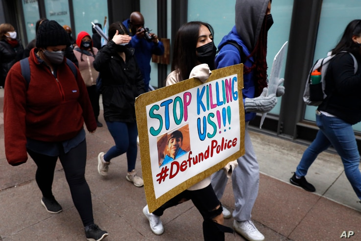 A protester holding a sign reading 'Stop Killing Us' navigates along Chicago's Loop during a peaceful protest, Wednesday, April...