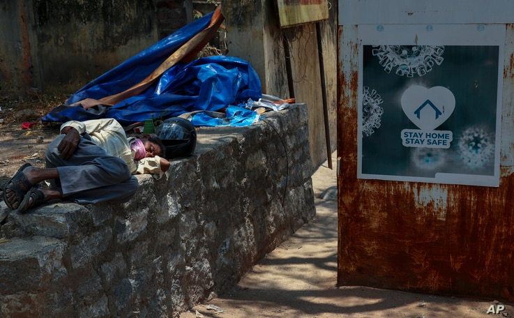 An Indian man sleeps next to a signage urging people to stay at home as a precaution against coronavirus in the premises of a…