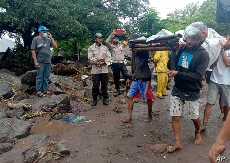 People carry a man injured during a flood in Ile Ape, on Lembata Island, East Nusa Tenggara province, Indonesia, Sunday, April…