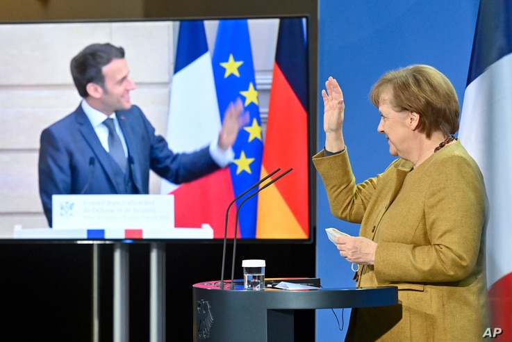 German Chancellor Angela Merkel waves to French President Emmanuel Macron at the end of a press conference following German...