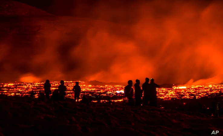People watch as lava flows from an eruption of a volcano on the Reykjanes Peninsula in southwestern Iceland late on Wednesday,…