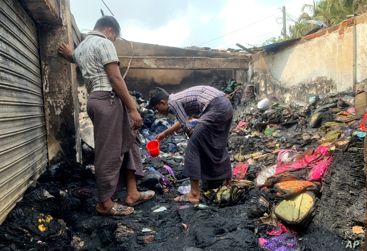 People inspect the debris after a fire in a makeshift market near a Rohingya refugee camp in Kutupalong, Bangladesh, Friday,…