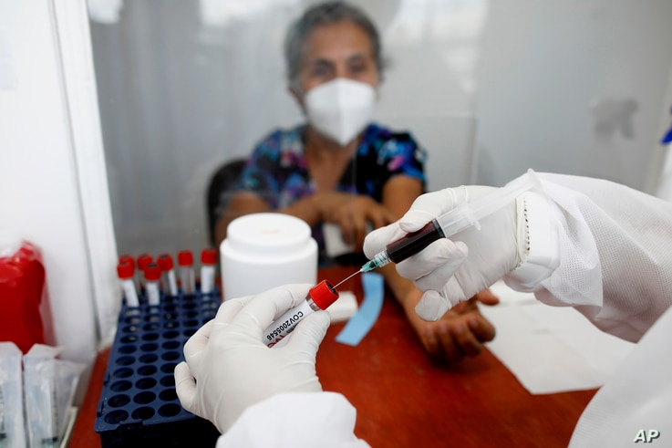Norma Gonzalez, 68, waits for results after she was tested for the COVID-19 virus, in a Red Cross laboratory in Tegucigalpa,…