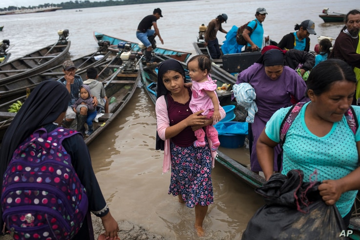 Members of the Israelites of the New Universal Pact religious group, arrive at a weekend market along the banks of  the Amazon…